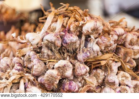 Close-up On A Stack Of Garlics On A Market Stall.