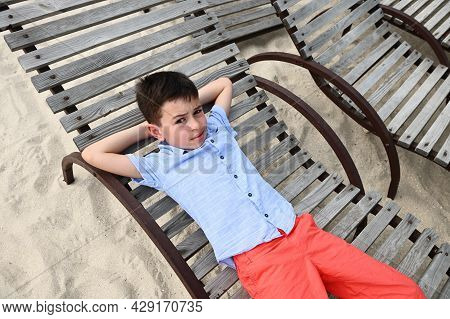 High Angle View Of A Happy Teenage Boy Lying Down On A Wooden Chaise Lounge. Handsome Kid Resting On