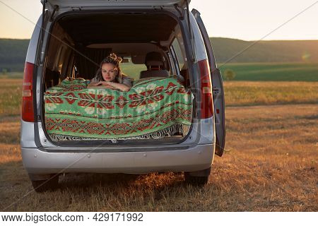 A Hipster Girl Lies In Bed In A Minivan Against The Background Of The Field And The Setting Sun. The
