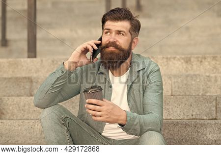Lets Communicate Through Call. Hipster Drink Coffee Talking On Smartphone Outdoors. Phone Conversati