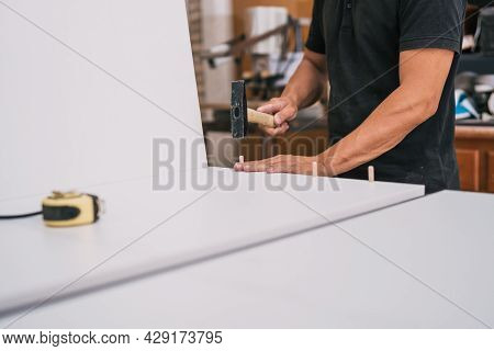 Worker Nailing Studs With A Hammer To A Piece Of Furniture In A Workshop