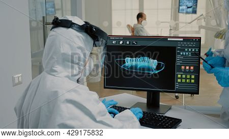 Team Of Orthodontists Examining Radiography Of Dentition On Modern Computer Monitor At Oral Clinic.