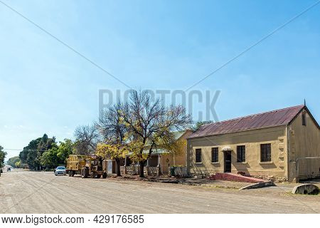 Rouxville, South Africa - April 23, 2021: A Street Scene, With Old Houses And A Tractor With Garbage