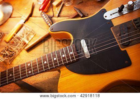 Guitar on guitar repair desk. Vintage electric guitar on a guitar repair work shop. Single cutaway electric guitar, amber color. poster
