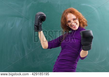 Smiling Teacher Wearing Black Boxing Gloves Celebrating Her Winning In Front Of Blank Green Chalkboa
