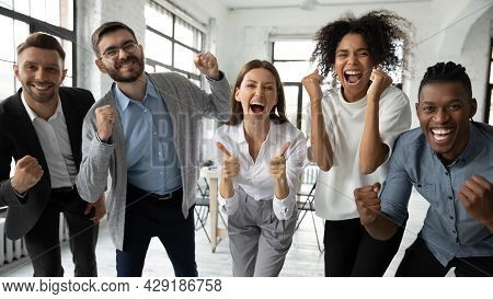 Portrait Of Excited Diverse Employees Celebrate Shared Success