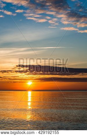 Sunset Over The Sea. Red And Yellow Sky In The Rays Of The Sunset. Reflection Of Sunlight In The Sea