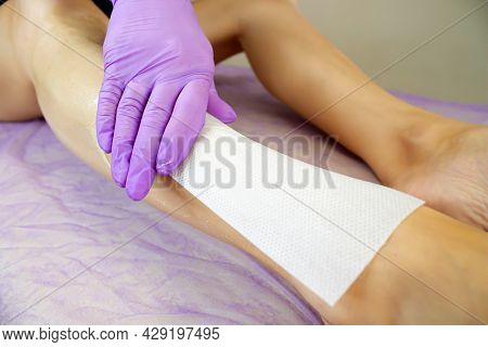 Wax Depilation. Epilation With Wax Strips. Hair Removal On The Legs. Gloved Hand And Wax Strip.