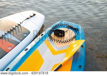Yellow Paddle Board And Two Surf Boards On Blue Clean Water Surface Background. Surfing And Sup Boar
