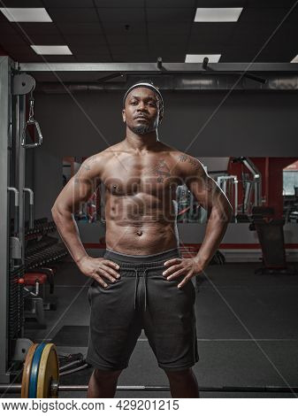 Muscular Athletic African American Guy With Naked Torso Posing On Training In Gym
