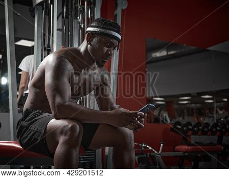 African American Athletic Guy With Phone Using Sports App For Exercising. Gym Workout And Technologi