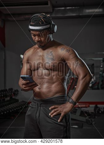 Athletic African American Man In Headphones With Phone Using Sport App During Training In Gym