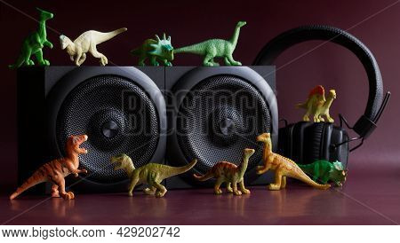 Toy Dinosaurs Next To Audio Speakers And Headphones. The Concept Of Decorating A Children's Room, Ch