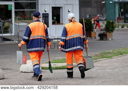 Two Female Janitors Walking On The Street. Cleaning City At Summer, Women With Brooms