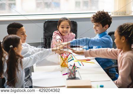 Happy Multiethnic Schoolchildren Putting Hands Together At Classroom