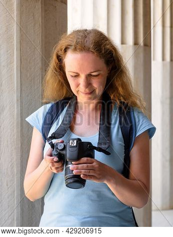 Young Woman In Stoa Of Attalos, Athens, Greece, Europe. Happy Female Tourist Plays Images In Camera.