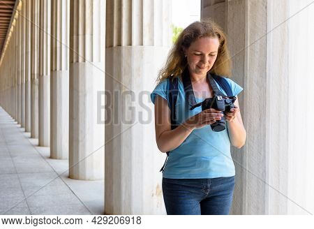 Female Tourist In Stoa Of Attalos, Athens, Greece, Europe. Young Woman Plays Images In Camera At Anc