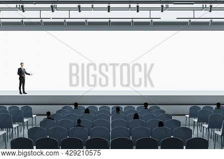 Business Man Standing In Modern Grey Auditorium With Seating And Empty Screen With Mock Up Place For