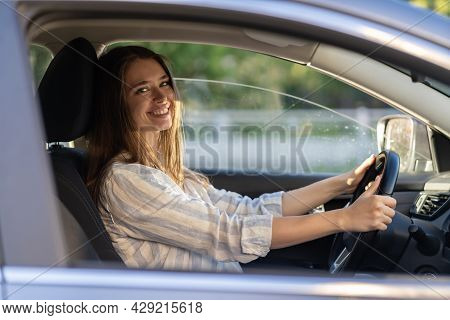 Happy Young Girl Sitting On Driver Seat In New Car Joyful Smiling Hold Hands On Wheel. Cheerful Fema