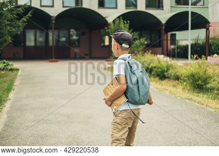 The Boy, Elementary School Student, Walking To School With Bag Behind Back And Book. Students Are Re