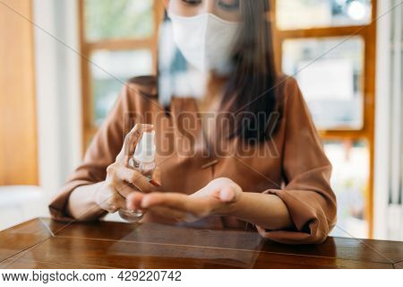 Young Asian Woman Wearing Covid-19 Protective Face Mask And Washing And Sanitizing Hands Using A Med