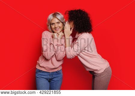 Red Background. Sisters Gossiping. Whispering At The Ear A Secret.
