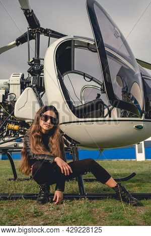 Smiling Tween Girl Sitting Near Open Helicopter On Flying Field