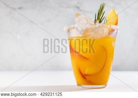 Bright Fruit Summer Beverage With Ripe Peach, Ice, Green Rosemary Twig, Sugar Rim, Fruit Pieces In M