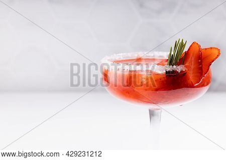 Fresh Classic Strawberry Margarita Cocktail With Green Rosemary Twig, Ice Cube, Fruit Slices, Sugar