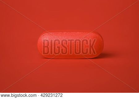Close up of a single pill tablet in red. Concept for single dose drug, prescription, or medical cure. Blank copy space on pill.