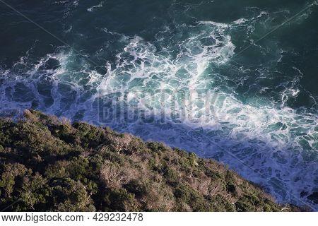 Waves Crash On Shore, Drone Aerial Shot Of Swirling Wild Ocean Coastline. Shadows On Water On Empty