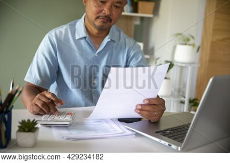 Budget And Tax Planning Concept, Accountant Is Calculating Company Annual Tax And Using Laptop. Pers