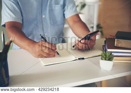 Man Hand Of Planner Writing And Plan Daily Appointment On Smartphone. Man Mark And Noted Schedule (h