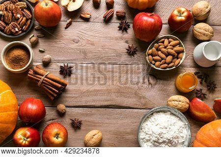 Autumn Fall Baking Background With Pumpkins, Aples, Nuts, Food Ingredients And Seasonal Spices. Cook