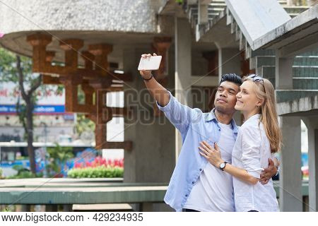 Happy Multi-ethnic Couple In Love Hugging And Taking Selfie On Smartphone