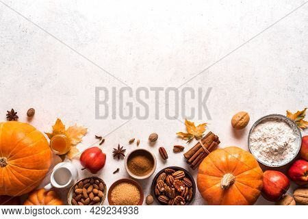 Autumn Fall Baking Food Background With Pumpkins, Apples, Nuts And Seasonal Spices On White. Cooking