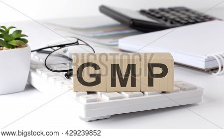 Good Manufacturing Practice. Gmp Written On A Wooden Cube On The Keyboard With Office Tools
