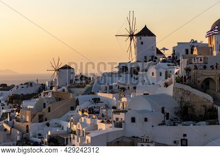 Oia, Santorini, Greece - June 28, 2021: Whitewashed Houses And Windmills In Oia In Warm Rays Of Suns