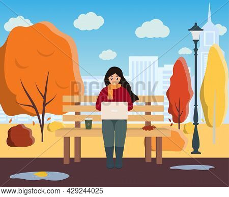 Young Woman Freelancer With Laptop And Coffee Sitting On The Bench In The Park. Autumn City Landscap