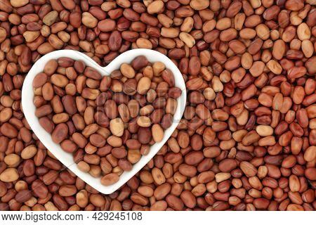 Fava beans, broad beans, in a heart shaped bowl. Vegan and vegetarian organic health food high in fibre, vitamins, minerals with many nutritional health benefits. Flat lay, top view.