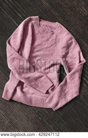 Pink Wool Crumpled Pullover On Dark Brown Wood Background