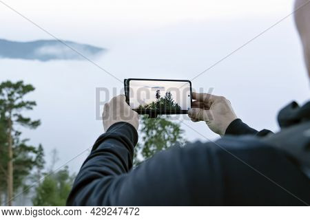 Morning Misty Forest, A Man Takes Pictures Of Nature On A Smartphone Camera. The Morning Dawn Is Met
