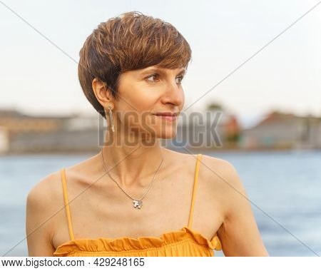 Portrait Of Beautiful Mature Woman With Short Brown Hair Standing On River Embankment In City Of St.