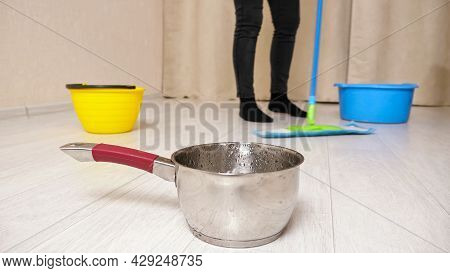 Water Comes Down Into Metal Saucepot From Ceiling After Rain While Woman Mops Wet Floor With Colorfu