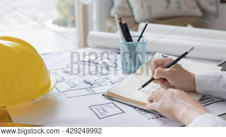 Architectural building design and construction plans with blueprints, young man is taking notes and