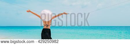 Summer vacation beach fun happy tourist woman enjoying sun carefree with open arms of happiness at Caribbean travel holiday wearing hat as solar skincare protection. Banner crop landscape background.