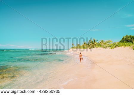 Caribbean beach travel vacation destination woman tourist walking alone on secluded coastline in tropical getaway.