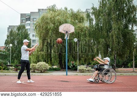 Dad Plays With His Disabled Son On The Sports Ground. Concept Wheelchair, Disabled Person, Fulfillin
