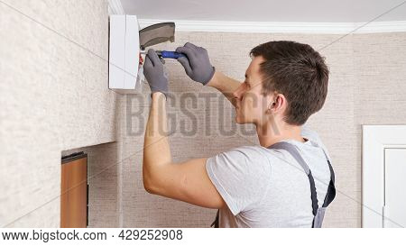 Concentrated Young Worker In Uniform Twists Screws On Contemporary Switchboard With Plastic Case Abo