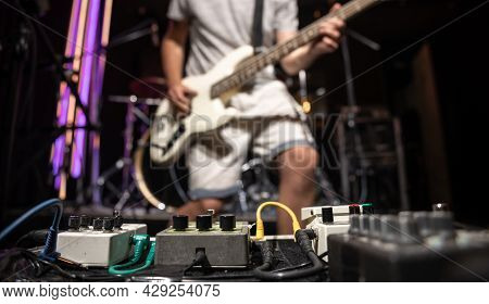 Bass Guitar Player On A Stage With Set Of Distortion Effect Pedals.